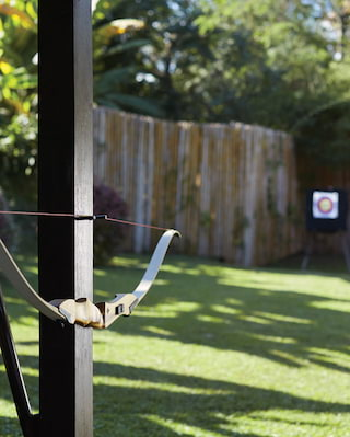 Archery bow hanging on a wooden pillar with three targets in the distance