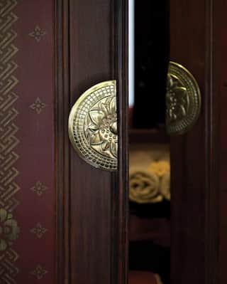 Close-up of teakwood doors with gleaming gold semi-circle handles