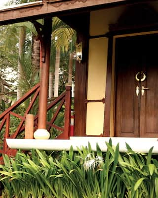 Steps leading to an oriental bungalow surrounded by lush gardens