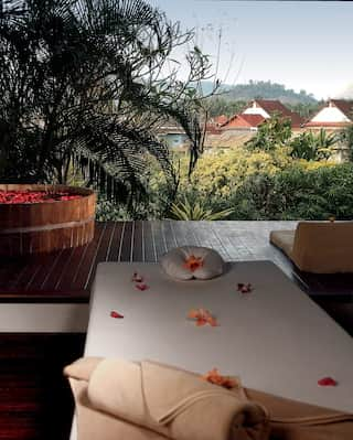 Spa treatment room with flower petals on a bed overlooking open-air terrace