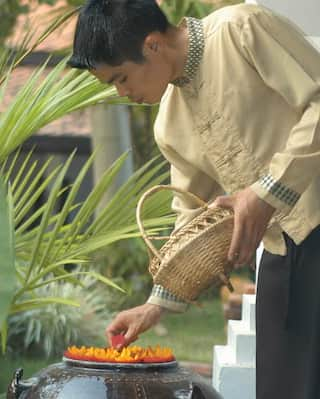 Spa therapist adding petals to a decorative plant pot containing water