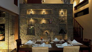 Villa dining area with Inca stone wall display in the background