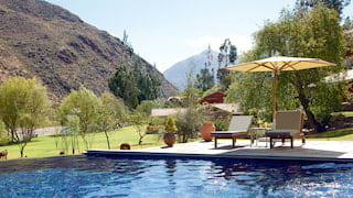 Outdoor hotel infinity pool overlooking Sacred Valley with two sun chairs under a parasol