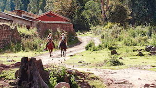 Two horseback riders trotting along a path in Sacred Valley