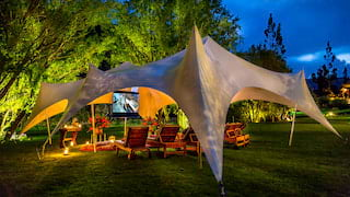 Glowing tent in gardens at night with a seating and a TV screen