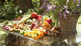 Selection of vegetables piled on a glass table with a lavender plant nearby