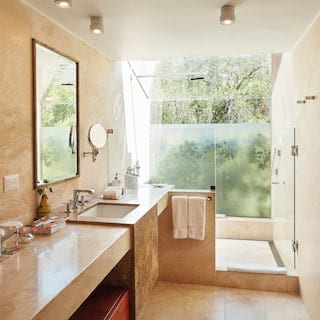 Luxurious bathroom with a walk-in shower surrounded by beige polished marble tiles