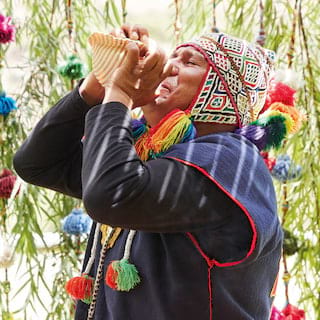 Traditional Peruvian shaman blowing a conch among brightly coloured hanging decorations