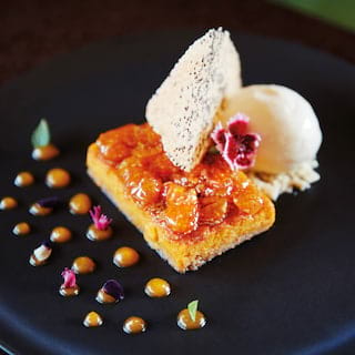 Close-up of a sweet Peruvian desert with ice cream on a black circular plate