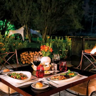 Restaurant terrace at night with a table laden with contemporary Peruvian cuisine