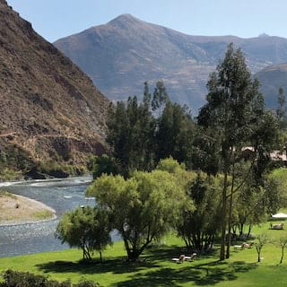Manicured hotel gardens alongside the Urubamba River in a mountainous valley