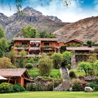 Collection of villa style buildings spilling down a hillside in Sacred Valley