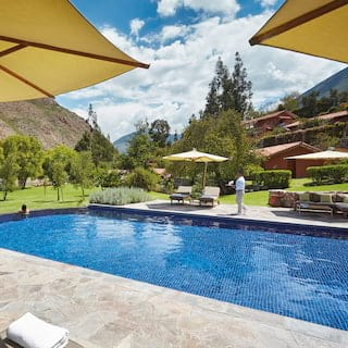 Outdoor pool surrounded by parasols and sunbeds under sunny blue skies