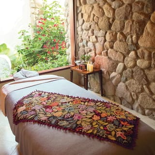 Spa treatment bed with a vibrant floral blanket on top, overlooking gardens