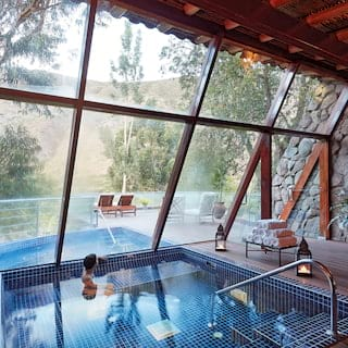 Lady swimming in a plunge pool with floor to ceiling windows overlooking the treetops of Sacred Valley