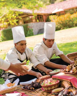 Two smiling chefs preparing an outdoor buffet lunch