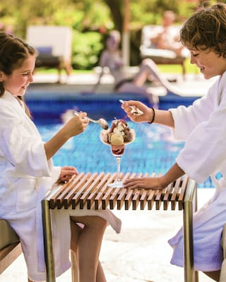 Two ladies in bathrobes at an outdoor poolside sharing an ice cream sundae