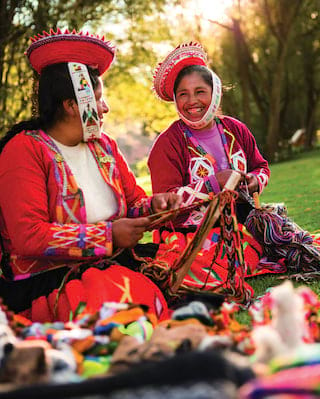 Smiling ladies in traditional Peruvian dress playing instruments