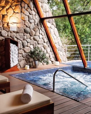 Spa jacuzzi surrounded by loungers and overlooking the treetops of Sacred Valley