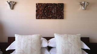 Close-up of cushions on a plush bed with ornate carved teakwood wall art above