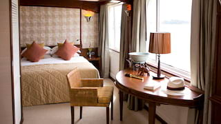 Spacious cruise ship suite with a large bed, writing desk and big picture windows