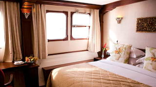 Pillowy king bed with floral-patterned cushions in a light-filled ship cabin