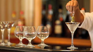 Close-up of a barman adding two olives to a martini glass on a polished bar top