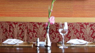 Cruise ship restaurant with red silk fabrics and ornate carved wood wall art