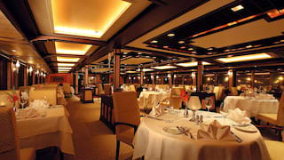 Lamplit restaurant with linen-topped tables and fan-shaped linen napkins