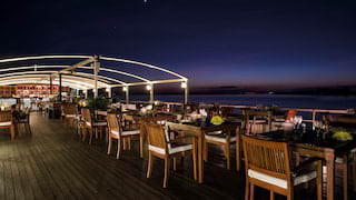 Wooden restaurant tables and chairs on a ship's top deck under the night sky