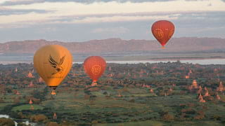 Red and yellow hot-air-balloons floating above grassy plains dotted with temples