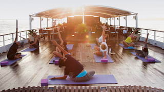 Ladies in yoga poses on purple yoga mats on the top deck of a ship at sunrise