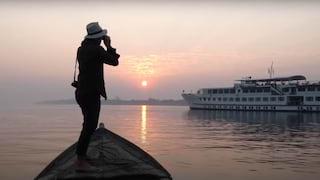 Lady with binoculars on a small sailing boat gazing towards a purple sunrise