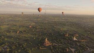 Red balloon rising into sunrise over Bagan, Myanmar