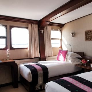 Cruise ship cabin with plush twin beds, writing desk and vibrant pink accents