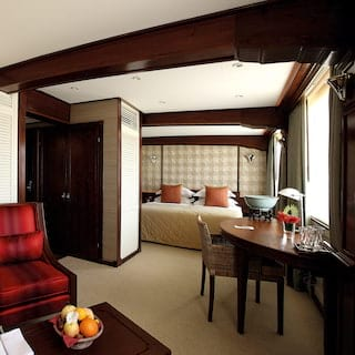 Vast cruise ship cabin suite with teakwood furnishings and spacious lounge area