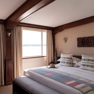 Vast pillowy bed in a sunlight-filled cruise ship cabin with large picture windows