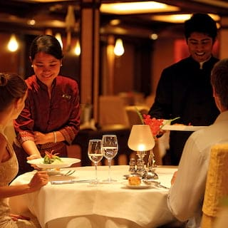 Smiling waiters serving dishes to a couple at a candlelit table for two