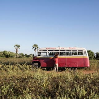 Red camper van in a field of grass and shrubs under bright blue skies