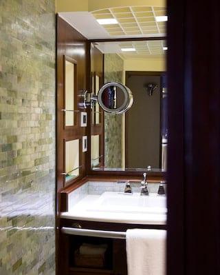 Cruise ship cabin bathroom with jade green tiles and white ceramic washbasin