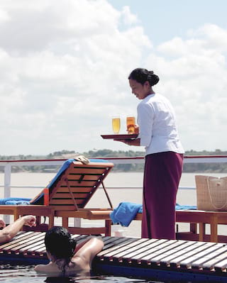 Bar stewardess carrying a tray of cocktails across a ship's deck