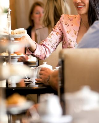 Smiling guests at rows of tables with tiered cake stands and porcelain tea pots