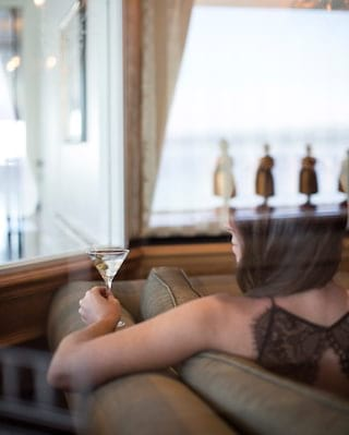 View through a window of a lady in a black lace dress holding a martini glass
