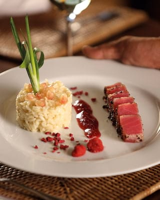 Close-up of a spring onion mash and carpaccio beef on a white circular plate