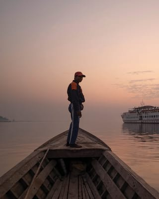 Man standing atop a wooden boat on the Ayeyarwady River