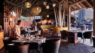 Open-air luxury restaurant hut with chocolate-coloured accents and rattan chandeliers
