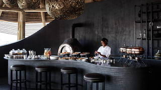 Curved ebony bar with black leather-topped bar stools and giant rattan lantern lights