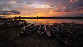 Mokoro canoes stabled on the shore of a river delta under cloudy skies at sunrise