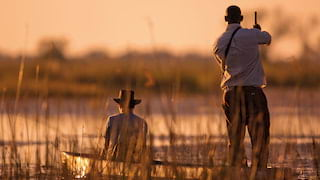 Safari guide pushing a traditional mokoro canoe through waterlogged grasslands at sunrise
