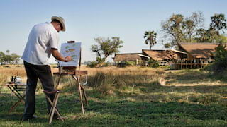 Man painting a canvas on an easel among grasslands overlooking safari lodges